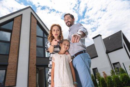 Photo pour Notre achat. Agréable famille heureuse debout devant leur nouvelle maison tout en vous pointant du doigt - image libre de droit