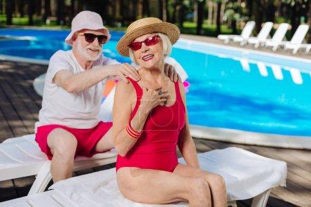 Photo pour Mari attentionné. Mari attentionné, mettant soleil de protection crème sur sa femme tout en un bain de soleil près de la piscine - image libre de droit