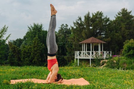 Photo for Perfect headstand. Experienced yoga woman feeling calm and free while practicing perfect headstand - Royalty Free Image