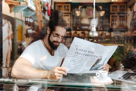 Homme beau intelligent tenant un journal