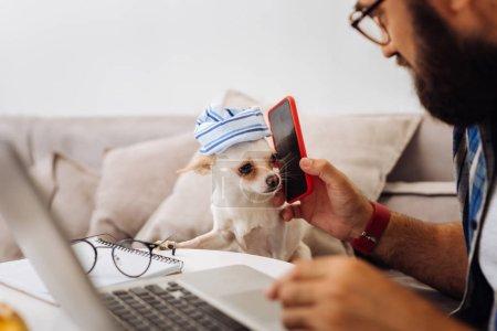 Photo pour Téléphone et chien. Barbu homme brun ayant tellement de plaisir tout en mettant son téléphone à l'oreille de son chien - image libre de droit