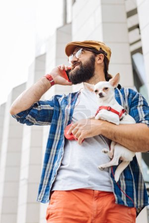 Dark-haired man walking the city with little white dog