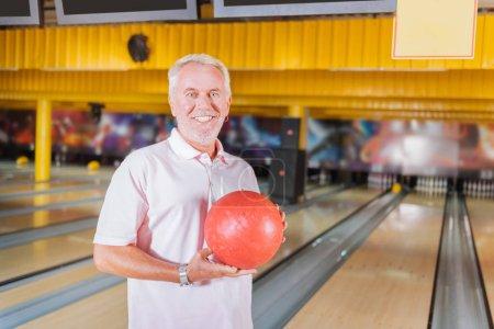 Joyful happy aged man holding a bowling ball