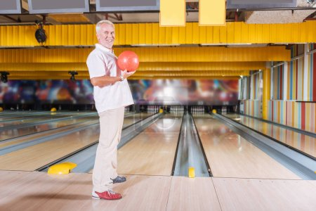 My turn. Pleasant joyful man holding a bowling ball while preparing to hit skittles