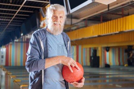 Pleasant senior man smiling in the bowling club