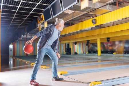 Nice bearded aged man playing bowling fervantly