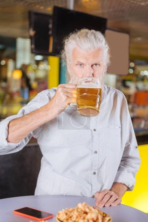 Delighted cheerful aged man drinking alcohol beverage