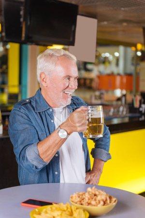 Positive joyful aged man taking a sip