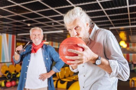 Serious aged man kissing the bowling ball