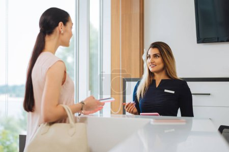 Nice pleasant woman taking to the receptionist