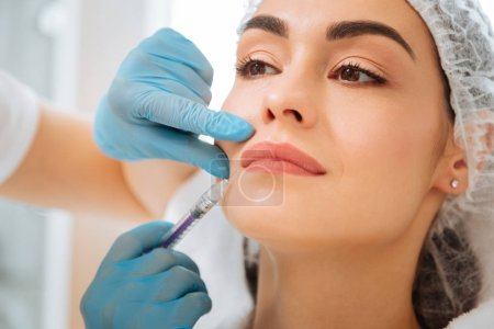 Nice beautiful woman having an injection in her face