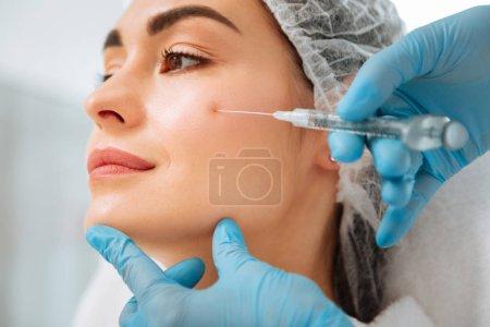 Photo pour Une peau parfaite. Gros plan d'une joue féminine pendant l'injection de beauté - image libre de droit