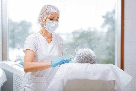 Photo pour Je me prépare. Femme intelligente sérieuse regardant son client tout en se préparant à faire une injection - image libre de droit