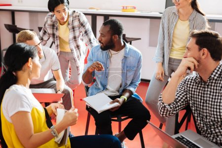 Introducing ideas. Smart hardworking student being surrounded by his group mates and holding his notebook while talking