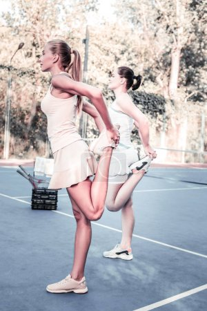 Photo for Quad stretch. Cheerful two women stretching on court and staying in profile - Royalty Free Image