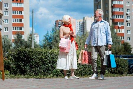 Photo pour Achats réussis. Toute la longueur de la famille âgée optimiste regardant les uns les autres tout en tenant les achats dans les mains et ayant une humeur lumineuse - image libre de droit