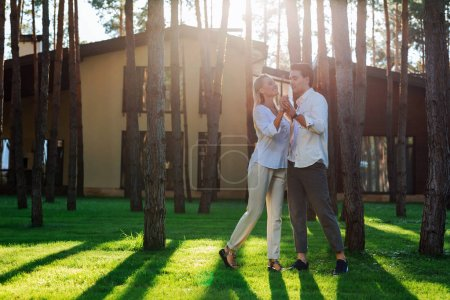 Photo for We are happy. Delighted nice couple dancing near their house while feeling happy - Royalty Free Image