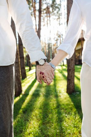 Photo for True love. Hands of nice positive couple being held together while walking in the woods - Royalty Free Image