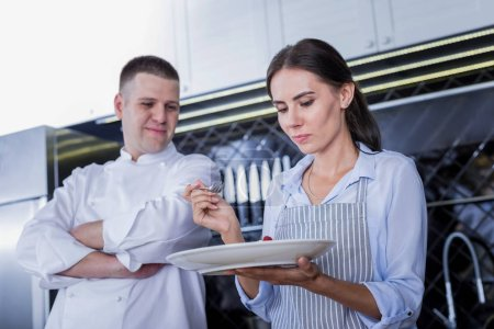 Pleasant chef and young cook trying a dessert