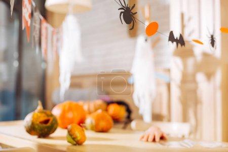 Foto de Listo para Halloween. Mesa con decoraciones de papel y calabazas brillantes tumbadas en ella lista para la fiesta de Halloween de los niños - Imagen libre de derechos
