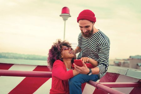 Photo for Couple with gadget. Cheerful young man smiling and looking at the screen of his smartphone while his loving girlfriend smiling to him - Royalty Free Image