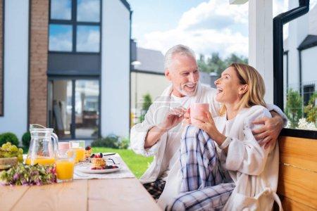 Photo pour Joli couple. Joli couple drôle d'homme mature et femme riant tout en plaisantant pendant le petit déjeuner délicieux - image libre de droit