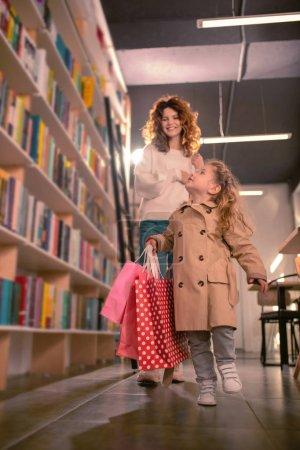 Photo pour Bibliothèque municipale. Joyeuse femme aux cheveux bouclés gardant le sourire sur son visage tout en fixant son enfant - image libre de droit