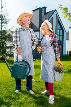 Photo pour Super moment. Couple retraité plein d'entrain se sentant heureux tout en passant du temps dans le jardin - image libre de droit