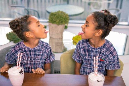 Kids cafe. Two curly dark-haired siblings feeling ...