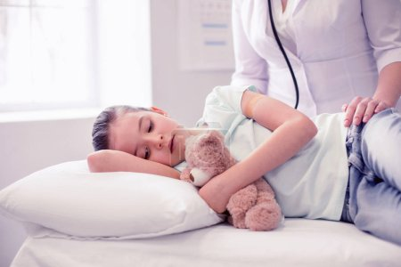 Photo for Lying on bed. Little cute girl wearing blue shirt feeling very sick lying on bed in hospital with her toy - Royalty Free Image