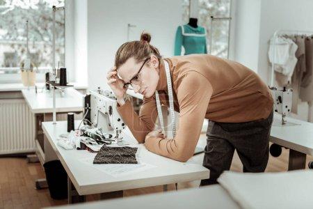 langhaarige Modeschneiderin in braunem Gewand wirkt nachdenklich
