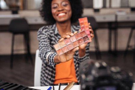 Photo pour Couleurs vives. Beau modèle brune aux cheveux bouclés, souriant tout en démontrant la nouvelle palette de couleurs - image libre de droit