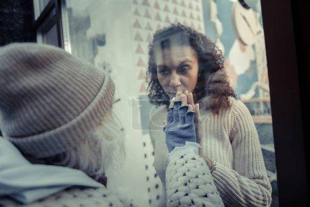Photo pour Rentre. Belle jeune femme ouvrant la porte de la cafétéria tout en demandant à la femme âgée de venir à l'intérieur - image libre de droit