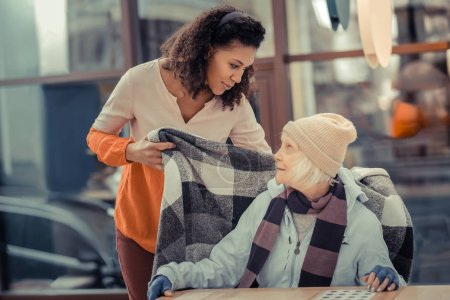 Photo for Would you like anything. Pleasant kind woman talking to her guest while taking care of her - Royalty Free Image