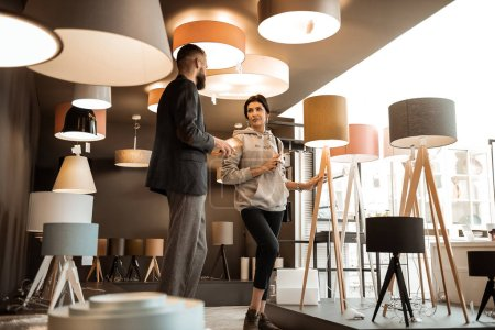 Photo for Filled showroom. Active couple standing in room filled with lightning equipment and having conversation with male consultant - Royalty Free Image