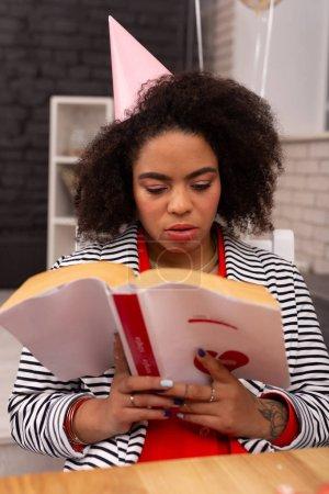 Photo pour Un roman d'amour. Agréable afro américain femme tenant un livre tout en le lisant - image libre de droit