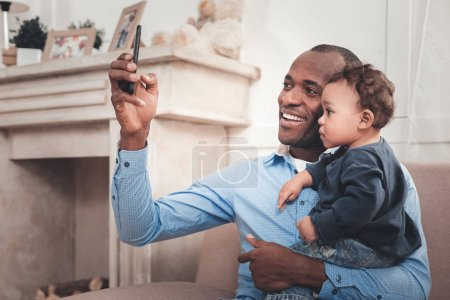 Photo for Family photo. Happy positive man taking a selfie while holding his baby - Royalty Free Image
