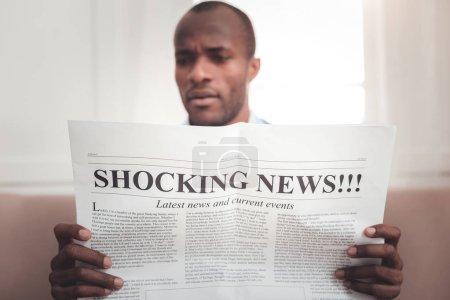Photo pour Dernières nouvelles. Mise au point sélective d'un journal étant dans les mains d'un beau jeune homme tout en lisant les nouvelles - image libre de droit
