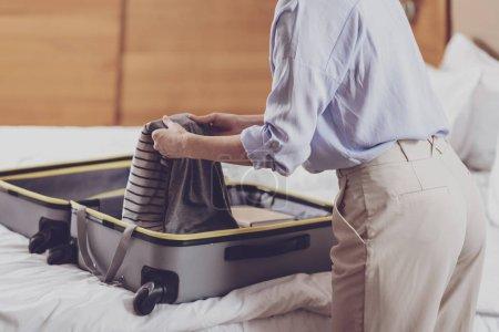 Photo pour Tout le nécessaire. Gros plan d'une femme optimiste agréable à vêtements pliant soigneusement ses affaires dans une valise en se tenant debout dans une chambre d'hôtel - image libre de droit
