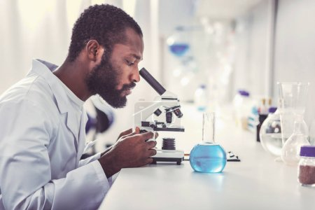 Photo for Chemical practitioner. Young chemical practitioner feeling busy while looking into modern microscope - Royalty Free Image