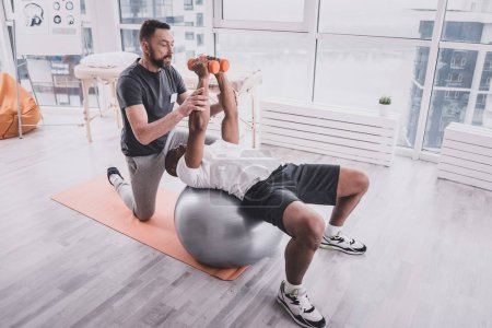Photo for Strong enough. Attentive African sportsman lifting dumbbells and lying on fitness ball - Royalty Free Image