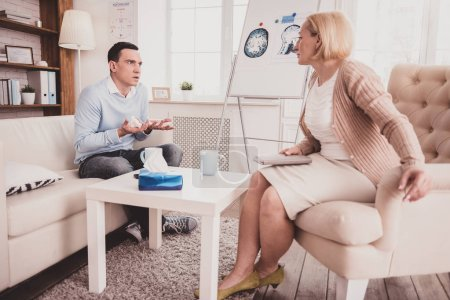 Photo for Help me. Attentive psychotherapist sitting in cozy armchair and analyzing the behavior of her patient - Royalty Free Image