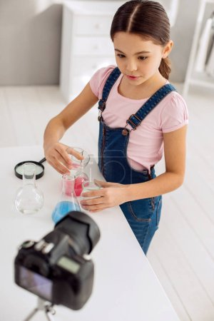 Photo for Exciting content. The top view of a pleasant pre-teen girl mixing chemicals and showing an interesting experiment to her viewers while recording it - Royalty Free Image