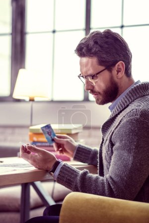 Photo for This is a sign. Serious thoughtful man reading the meaning of the card while having a fortunetelling session - Royalty Free Image