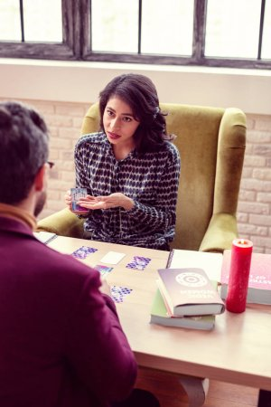 Photo for Seeing the future. Nice attractive woman holding tarot cards while trying to help her client - Royalty Free Image