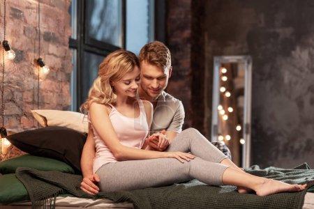 Photo pour Moment de détente. Cute loving couple étonnant porte pyjama passer moment de détente dans la chambre à coucher - image libre de droit