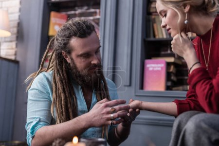 Photo for Palm reader. Positive bearded man looking at his clients hand while working as a chiromancer - Royalty Free Image