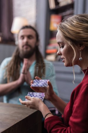 Photo for Tarot cards pack. Nice young woman shuffling the tarot cards while thinking about her destiny - Royalty Free Image