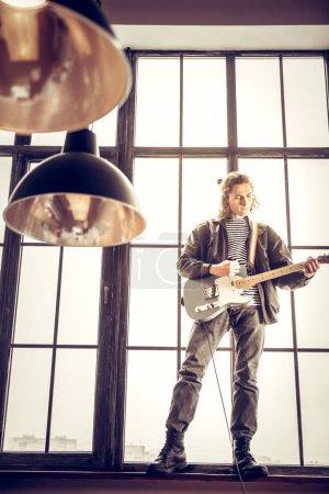 Photo pour Hard rock. Roche musicien portant bottes de cuir jouer hard rock debout sur le rebord de la fenêtre - image libre de droit