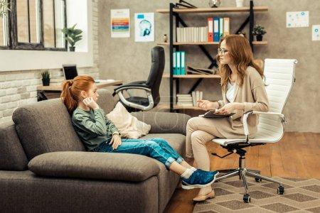 Photo pour Bonne humeur. Positif ravi femme assise sur la chaise tout en parlant avec sa jeune patiente - image libre de droit